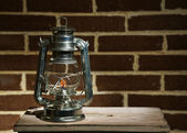 Burning kerosene lamp on brick wall background — Stock Photo