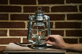Hand lights a kerosene lamp on brick wall background — Stock Photo