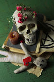 Conceptual photo of love magic. Composition with skull, voodoo doll, dried herbs and candle on  color wooden background — Stock Photo
