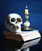 Skull and candle on old book  on dark color background — Stock Photo