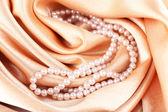 Beautiful pearls on golden silk cloth — Stock Photo