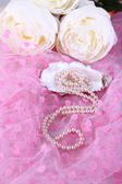 Beautiful pearls in shell on pink cloth — Stock Photo