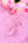 Krásné perličky na růžovou látkou — Stock fotografie