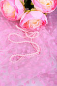 Beautiful pearls on pink cloth — Stock Photo