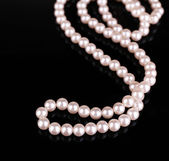 Beautiful pearls on black background — Stock Photo