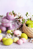 Composition with Easter eggs in glass jar and wicker basket, and blooming branches on light background — Stock Photo