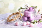 Composition with Easter eggs in glass jar and blooming branches on light background — Stockfoto