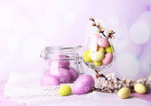 Composition with Easter eggs and blooming branches on light background — Stok fotoğraf