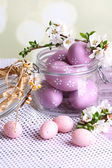 Composition with Easter eggs in glass jar and blooming branches on light background — Foto de Stock