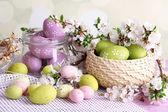 Sammansättning med påskägg i glasburk och rotting korg och blommande grenar på ljus bakgrund — Stockfoto