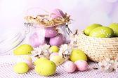 Samenstelling met Pasen eieren in glazen pot en rieten mand en bloeiende takken op lichte achtergrond — Stockfoto