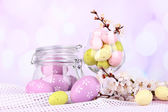 Composition with Easter eggs and blooming branches on light background — Stockfoto