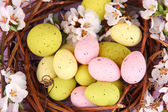 Composition with Easter eggs and blooming branches in nest, on wooden background — Stock Photo
