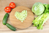 Heart shape of chopped celery  and fresh vegetables, on wooden background — Stock Photo