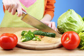 Female hands cutting cucumber on wooden board, close-up, on blue background — Stock Photo