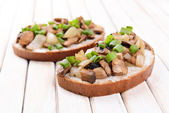 Delicious bruschetta with mushrooms on table close-up — Stock Photo
