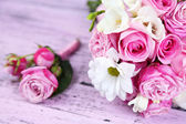 Beautiful wedding bouquet and boutonniere on wooden background — Stock Photo