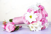 Beautiful wedding bouquet and boutonniere on table on light background — Stock Photo