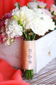 Beautiful wedding composition with bouquet  on table on fabric background  — Stock Photo