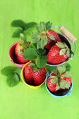 Strawberries with in decorative buckets on wooden background — Stock Photo