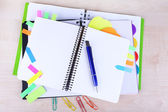 Notebook, pen, and stickers on wooden background — Stock Photo