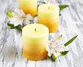 Lindas velas com flores sobre fundo de madeira — Fotografia Stock