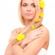 Beautiful young woman with a bright yellow chrysanthemums in her hair on white background close-up — Stock Photo