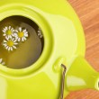 Teapot with chamomile tea on wooden table close-up — Stock Photo #44433379