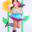 Beautiful young woman in petty skirt holding basket of flowers on decorative background — Stock Photo #44436437