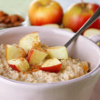 Tasty oatmeal with apples and cinnamon on table close up — Stock Photo #44438203