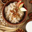 Tasty oatmeal with nuts and apples on wooden table — Stock Photo #44438231