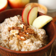 Tasty oatmeal with nuts and apples on table close up — Stock Photo #44438251