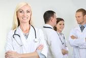 Lekarz stoi przed współpracowników na szarym tle — Zdjęcie stockowe