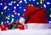 Santa hat on snow on lights background — Stock Photo