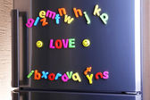 Word Love spelled out using colorful magnetic letters on refrigerator — Stock Photo