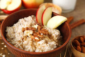 Tasty oatmeal with nuts and apples on table close up — Stock Photo