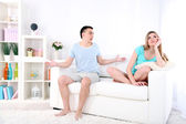 Young man and woman  conflict sitting on sofa argue unhappy, on home interior background — Foto de Stock