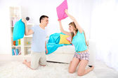 Couple fighting together with pillows on home interior background — Foto de Stock