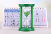 Hourglass and calendar on bright background — Stock Photo