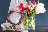 Composition with Easter eggs and beautiful tulips in glass jug on color wooden background — Stock Photo