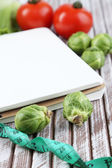 Notebook with measuring tape and vegetables on wooden background — Stockfoto