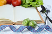 Book with cutlery,measuring tape and vegetables on wooden background — Stock Photo