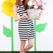 Beautiful young woman holding basket of flowers on decorative background — Stock Photo