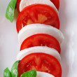 Caprese salad with mozarella cheese, tomatoes and basil on plate, close-up — Stock Photo