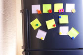 Empty paper sheets and colorful magnets on fridge door — Стоковое фото