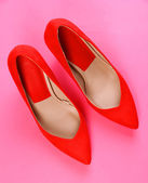 Beautiful red female shoes, on pink background — Stock Photo