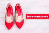 Beautiful red female shoes, on wooden background — Stock Photo