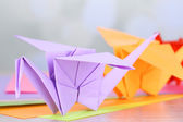 Origami cranes on wooden table, on light background — 图库照片