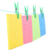Kitchen sponges hanging on rope isolated on white — Stock Photo