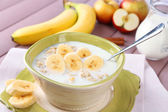 Tasty oatmeal with bananas and milk on wooden table — Stock Photo